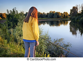 Girl with a fishing rod on the river Bank.