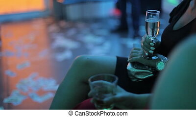 Girl with a glass of white wine in her hand at a party. The...