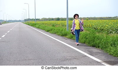 girl with a guitar hitch-hiking