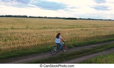 Girl with a guy riding a bike along a wheat field.Travel...