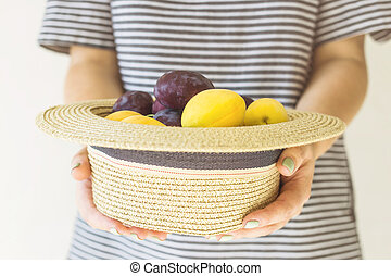 Girl with a hat full of fruit in the hands