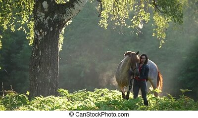Girl with a horse on a walk in the woods early in the...