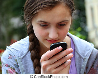 Girl with a mobile phone reads the message