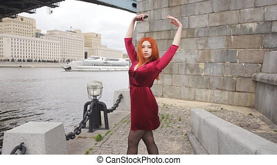 Girl with a phone in hand is dancing on the background of a passing ship