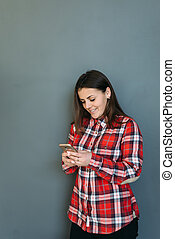 girl with a phone in hands is standing by the wall and smiling