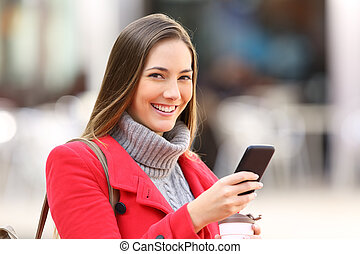Girl with a phone looking at you in winter