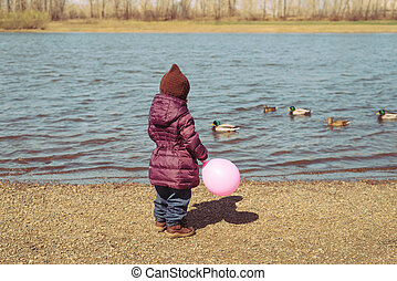 Girl with a pink baloon on riverbank