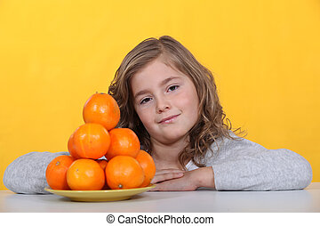 Girl with a pyramid of oranges