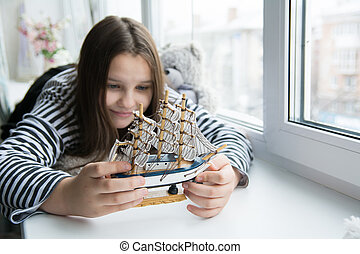 Girl with a ship on the window sill dreaming of voyages