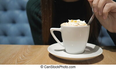 girl with a spoon tries foam with cappuccino.
