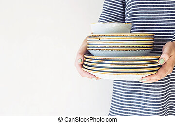 Girl with a stack of dishes in her hands
