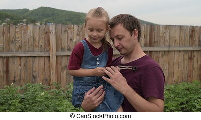 Girl with a strange toy hugging her dad - Little girl with a...