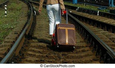 Girl with a suitcase. - Girl with a suitcase goes on rails.