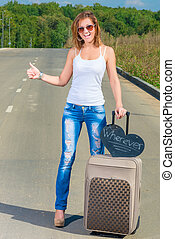 girl with a suitcase on the road traveling hitchhike