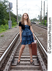 Girl with a suitcase standing on the rails