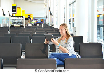 Girl with a tablet in the airport