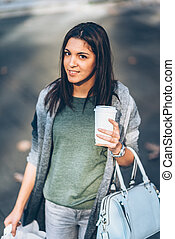 Girl with a take-away coffee shopping