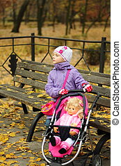 Girl with a toy stroller in autumn