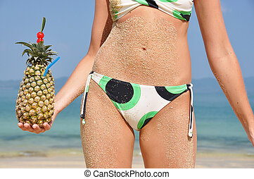 Girl with a tropical cocktail on the beach