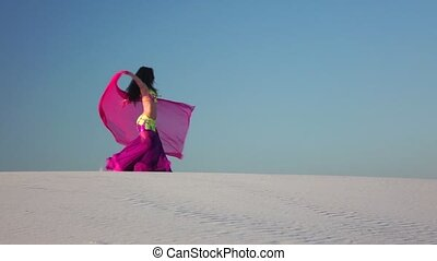Girl with a veil in her hands dances a belly dance in the desert. Slow motion