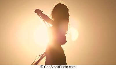 Girl with a veil in her hands dancing belly dance on the beach. Silhouette