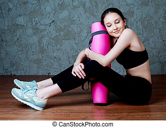 girl with a yoga mat - beautiful smiling teenage girl...