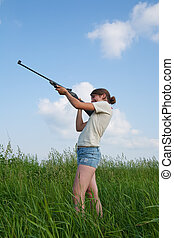 Girl with air rifle - young woman aiming a pneumatic air...