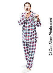 Girl with an alarm clock in checkered pajamas showing a...