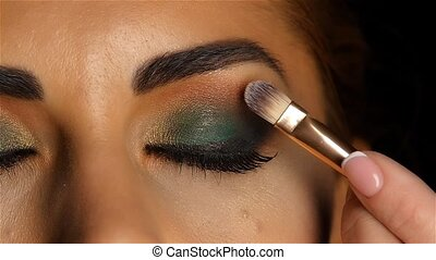 Girl with an evening make up with closed eyes, make up brush...