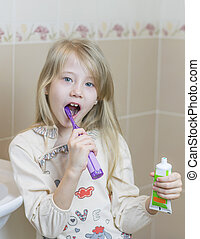 Girl with an open tube of toothpaste and an electric toothbrush.