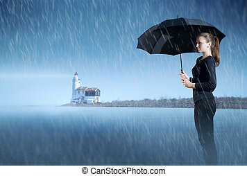 girl with an umbrella standing in the mist on the ocean at night in the rain, on the background of the lighthouse.