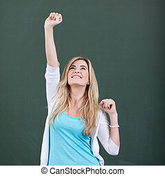 Girl With Arm Raised Celebrating Victory Against Chalkboard