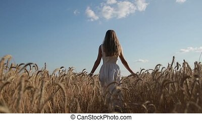 Girl with arms outstretched walking on wheat field -...