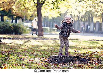 girl with autumn leaves in the beauty park