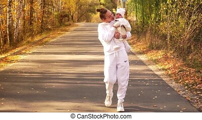 Girl with baby goes on the road in autumn