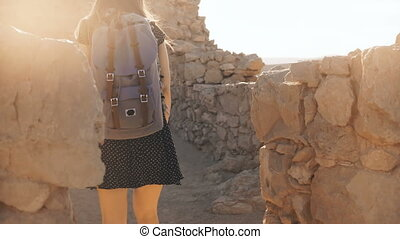 Girl with backpack explores ancient desert ruins. Pretty...