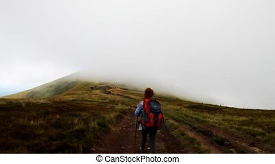 Back view of girl with sticks and backpack hiking mountains going to point of interest (pov)