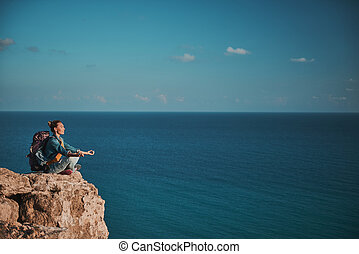 Girl with backpack meditating on the top - Profile of...