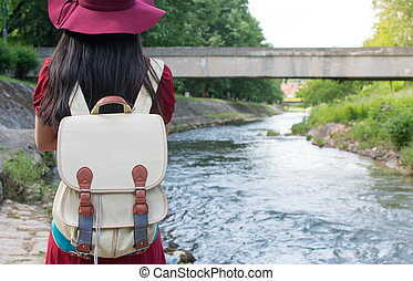 Girl with backpack standing in front of a river