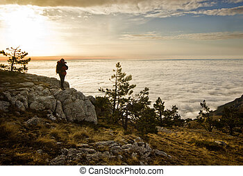 girl with backpack standing in the mountains at sunrise