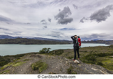 girl with backpack standing on the stone above lake in patagonia