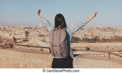Girl with backpack walks to see old Jerusalem town. Excited...