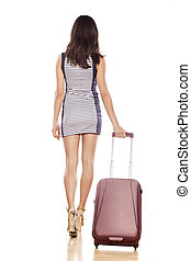 rear view young pretty woman in a short dress with a suitcase