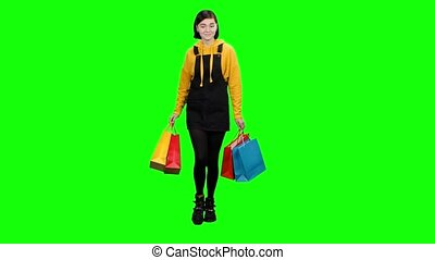 Girl with bags in her hands after shopping is happy shopping. Green screen