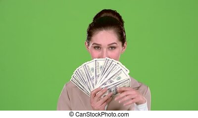 Girl with banknotes of money in her hands, winks at the guy she likes. Green screen
