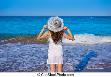 Girl with beach hat in sea open arms