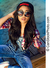 Girl with beautiful black hair in sunglasses sits near swimming pool