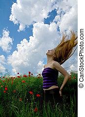 Girl with beautiful blond hair in splendid green meadow