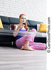 Girl With Beauty Mask Reading And Watching Television At Home