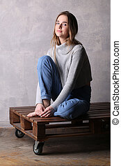 Girl with bended knee sitting on a deck. Gray background